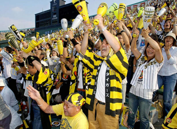 Поклонники Hanshin Tigers празднуют, как команда выиграла свой первый чемпионский титул за 18 лет на стадионе Koshien в Нисиномии, недалеко от Осаки, 15 сентября 2003 г.