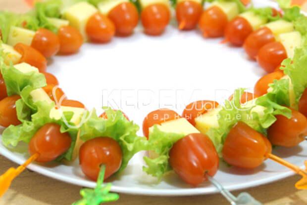 Добавить кубики сыра и вторые половинки помидорчиков. Выложить по кругу на блюдо.