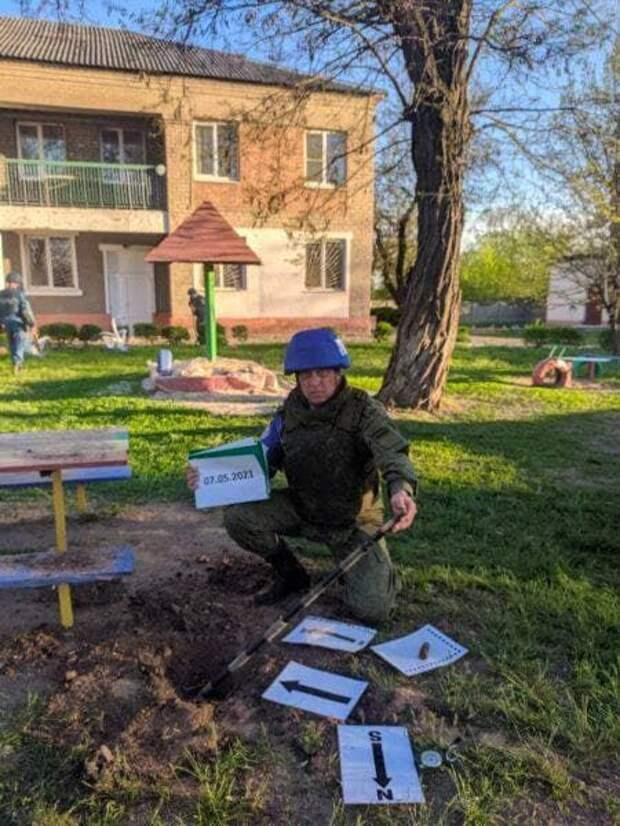 Офицер представительства ДНР в СЦКК измеряет воронку во дворе детского сада.