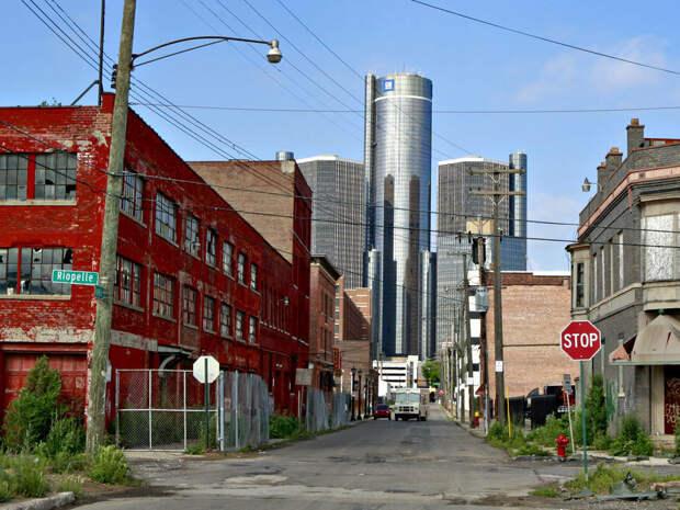 Детройт. Разрушенная почти полностью промышленность, на фоне блестящих небоскребов делового центра города. Вся промышленность загнулась, тысячи и сотни тысяч людей брошены, потому что капитал ушел и никому нет дела до людей.