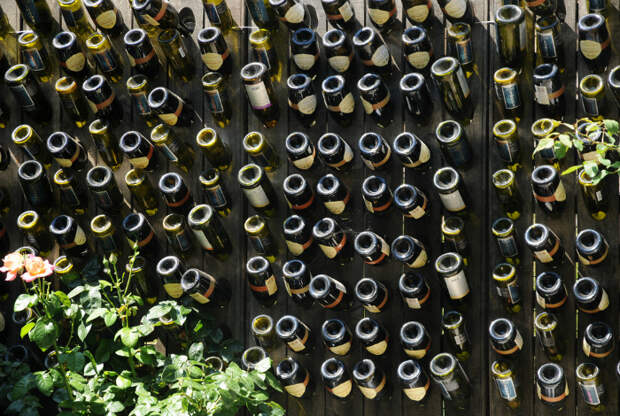Деревянный забор с винными бутылками. | Фото: Garden Lovers Club.
