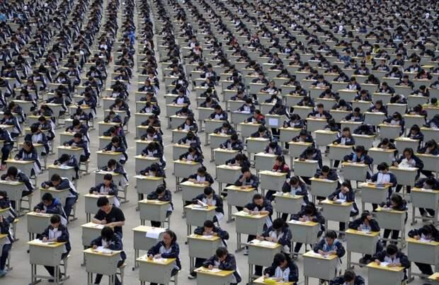 Ученики во время экзамена в старшей школе на школьной игровой площадке в Ичуане, провинция Шэньси. В 2015 году в экзамене участвовало более 1700 абитуриентов, и пришлось проводить его на улице, потому что в помещении было недостаточно места. китай, люди, население
