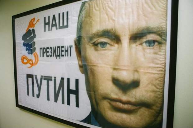 """In his office, G. Kline Preston IV displays a flag reading """"Our President Putin"""" that was given to him in the streets on Russia's last presidential election day. (Kyle Dean Reinford/For the Washington Post)"""