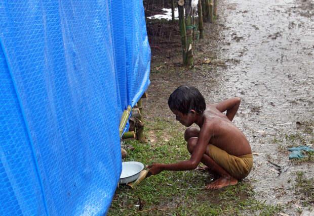Мальчик собирает дождевую воду, стекающую с палатки в лагере для людей, эвакуированных из-за циклона Nargis в административном округе города Лабутты (Labutta), столицы одноименного региона в дельте реки Иравади, расположенного в 320 км крупнейшего города Мьянмы Янгон. Фото сделано 31 мая 2008. В результате циклона Nargis, прошедшего в ночь на 2 мая, 133 тысяч человек погибли или остались без вести