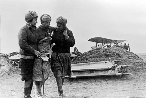 Санитарки ведут раненого красноармейца.