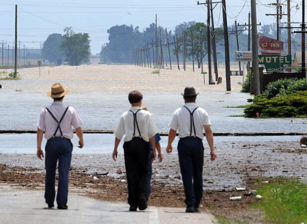 Четверо местных жителей-амишей в городе Worthington, штат Индиана идут к кромке воды затопленного Шоссе 67. (AP Photo/The Indianapolis Star, Matt Kryger)