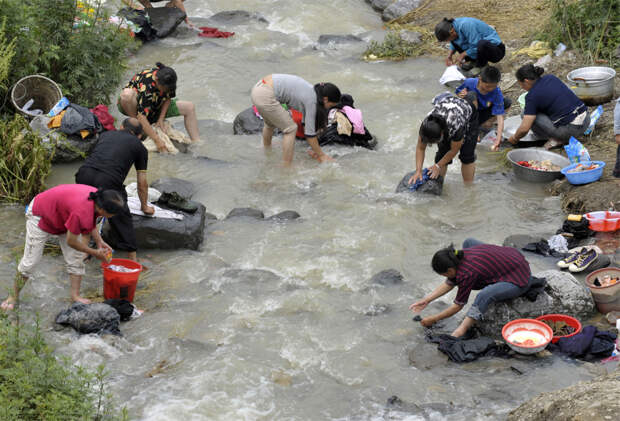 Оставшиеся в живых после землетрясения стирают белье в реке в городе Leigu уезда Бэйчуань, в юго-западной китайской провинции Сычуань 31 мая 2008. районе дамбы на озере-запруде Танцзяшань в китайской провинции Сычуань произошло землетрясение. Масштабы разрушений, вызванных им, пока не (AFP PHOTO/TEH Koon Eng)
