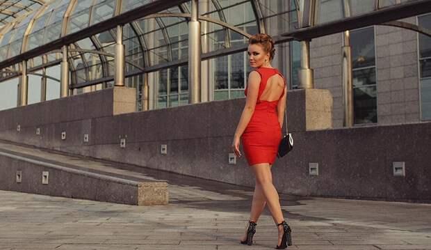 Хорошо одетая молодая женщина идет по улице