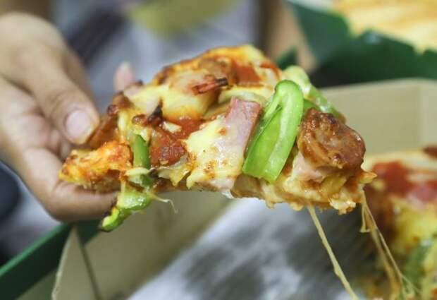 кусок пиццы в женской руке