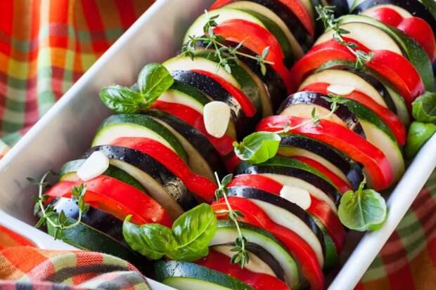 Налить на дно томатный соус, выложить сверху лук и чеснок. Приправить. Сверху разложить нарезанные овощи.