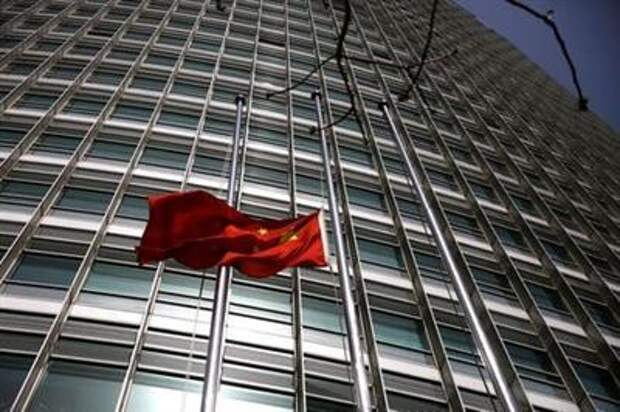 The Chinese national flag flies at half-mast outside a bank in Beijing, as China holds a national mourning for those who died of the coronavirus disease (COVID-19), on the Qingming tomb-sweeping festival, April 4, 2020. REUTERS/Tingshu Wang