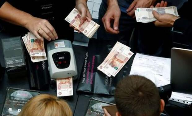 A shop assistant (L) counts Russian rouble banknotes as customers gather at a store selling Apple products during the launch of the new iPhone 7 sales at the State Department Store, GUM, in central Moscow, Russia September 23, 2016. REUTERS/Sergei Karpukhin