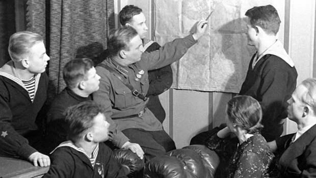 Валерий Чкалов показывает на карте маршрут своего перелета из Москвы в Ванкуверморякам с крейсера «Марат» и рабочим с московской кондитерской фабрики имени Марата