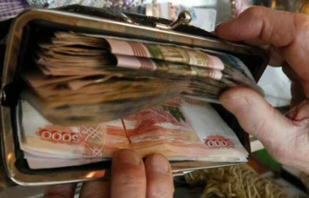 A vendor places Russian rouble banknotes earned during the day into a purse at a home appliances shop in the Siberian city of Krasnoyarsk, Russia, January 11, 2016. Russia's rouble fell further on January 20, setting a new record low of over 81 roubles per dollar as a bearish mood gripped Russian financial markets. Picture taken January 11, 2016. REUTERS/Ilya Naymushin