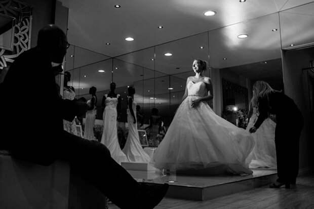Улыбающаяся Стефани примеряет платье с длинным шлейфом. Фото: James Day.