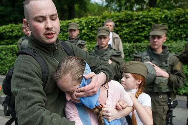 Украинские  нацисты  срывают  с  женщины и    девочки   георгиевские  ленты.  Киев,  2016  год.  Изображение  из  открытых  источников.