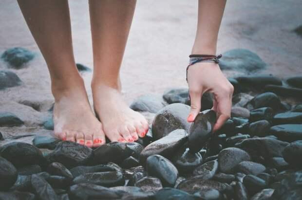 девушка поднимает камень на пляже