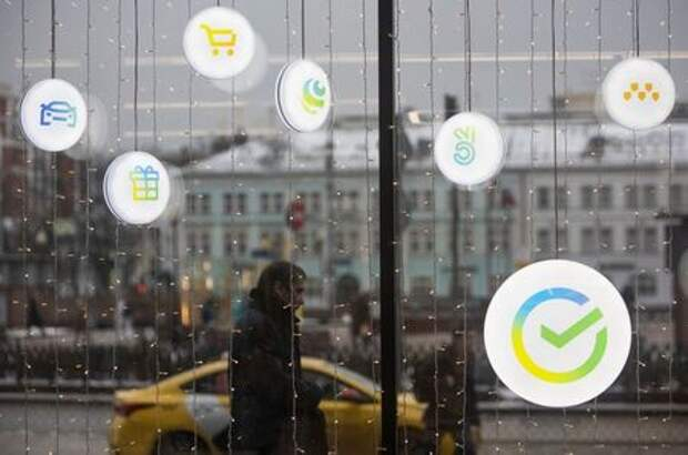 A man walks past an office of the Russian largest lender Sberbank in Moscow, Russia December 24, 2020. The logos of Sberbank ecosystem companies, which launched campaigns and new market, delivery, taxi and online cinema services, are displayed on an office window. Picture taken December 24, 2020. REUTERS/Maxim Shemetov