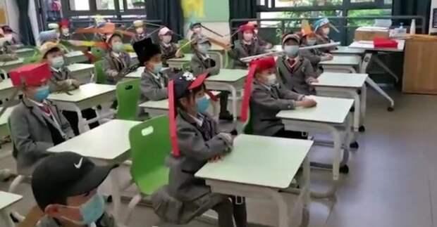 Китайские дети ходят в школу в смешных шляпах для социального дистанцирования
