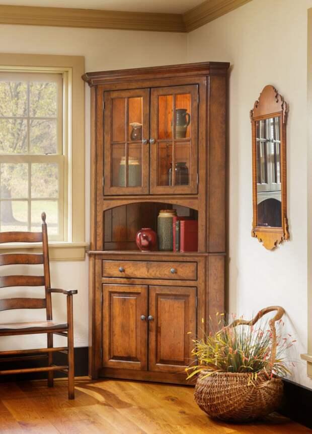Добротный деревянный буфет в углу поможет сэкономить пространство в дачном домике