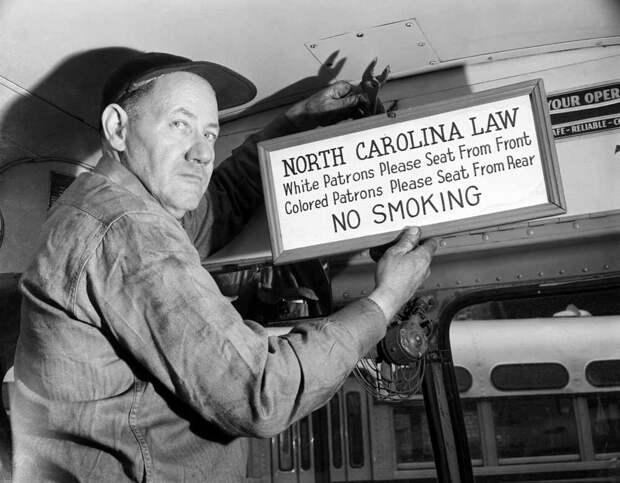 Водитель автобуса внутри пассажирского салона с табличкой в которой сказано, что белым пассажирам следует садиться на передние ряды сидений, а цветные - должны размещаться на задних