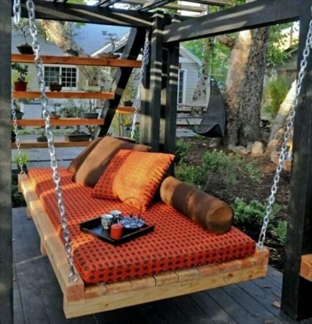 Оригинальная подвесная кровать, сделанная из старых деревянных поддонов и мягкого матраса, станет незаменимой деталью современного дачного участка.