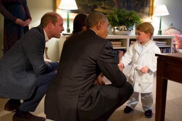 Президент США Барак Обама и первая леди Мишель Обама (на заднем плане) встречаются с принцем Джорджем в Кенсингтонском дворце в Лондоне.