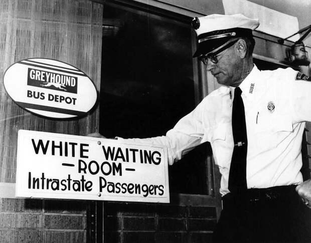 Полицейский у входа в помещение автовокзала с надписью Комната ожидания для белых