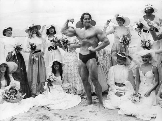 Арнольд Шварценеггер позирует на пляже, окруженный девушками на 30-м Каннском кинофестивале 1977-го года.