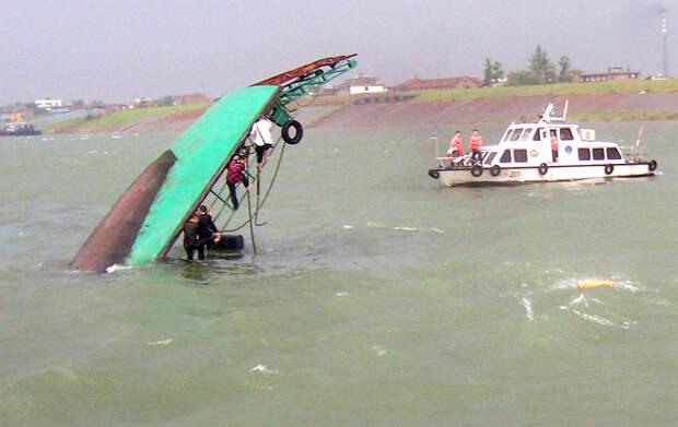 Пассажиры висят, уцепившись за перевернутый паром, в ожидании спасателей. Авария, во время которой семеро человек пропали без вести, произошла в результате внезапного повышения воды в реке Чжицзян, притоке Янцзы, после мощной грозы, которая пронеслась по уезду Чжицзян в центральной провинции Хубэй 3 июня 2008. Проливные ливни в Китае к июню 2008 унесли 64 жизни, вызвав сильные наводнения, уничтожив тысячи домов, мосты и посевы. (AFP/AFP/Getty Images)