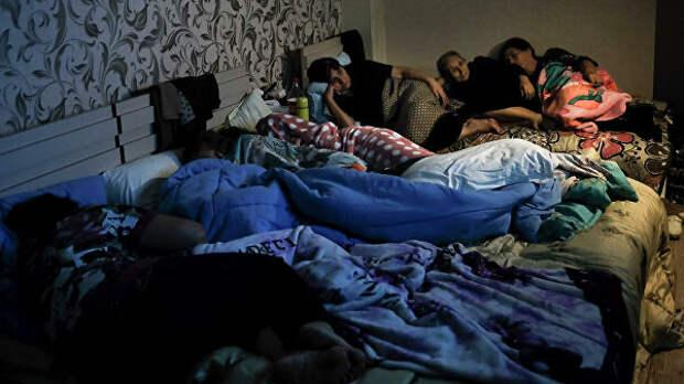 Люди смотрят телевизор в бомбоубежище в Степанакерте