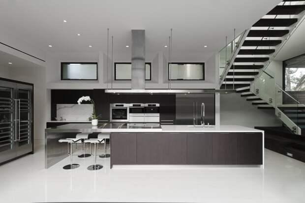 Очень просторная кухня-студия в строгой цветовой гамме несмотря на скупость красок выглядит очень комфортно