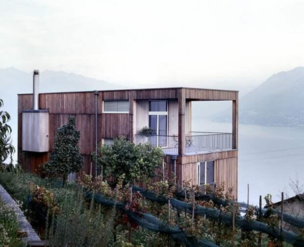Современный дом с деревянной обшивкой, большой террасой и шикарным видом на озеро и горы.