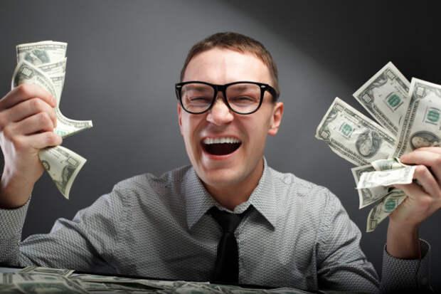 парень в очках улыбается с долларами в руках
