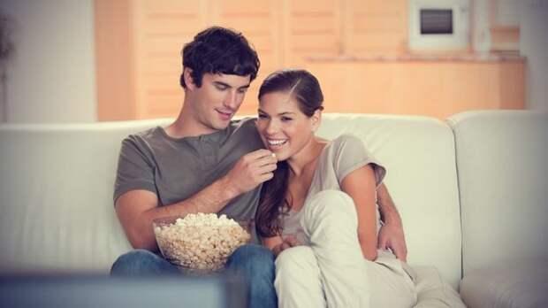 пара ест попкорн и смотрит фильм, сидя на диване