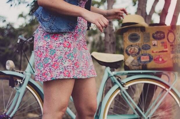девушка стоит рядом с велосипедом