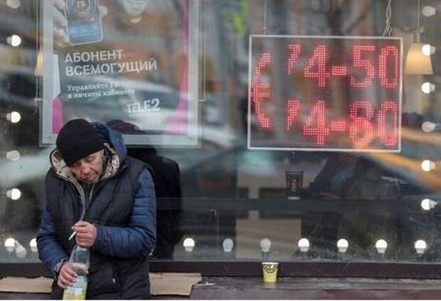 A man smokes next to a window with a board, showing the currency exchange rates of the Euro against the Russian rouble, on a street in Moscow, Russia February 28, 2020.REUTERS/Evgenia Novozhenina