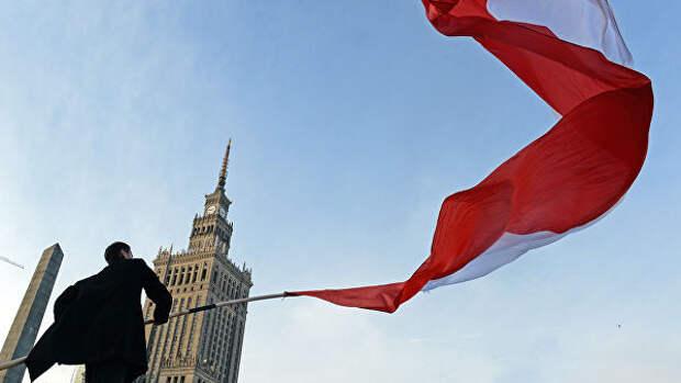 Мужчина держит польский флаг во время празднования Дня независимости в Варшаве. Архивное фото