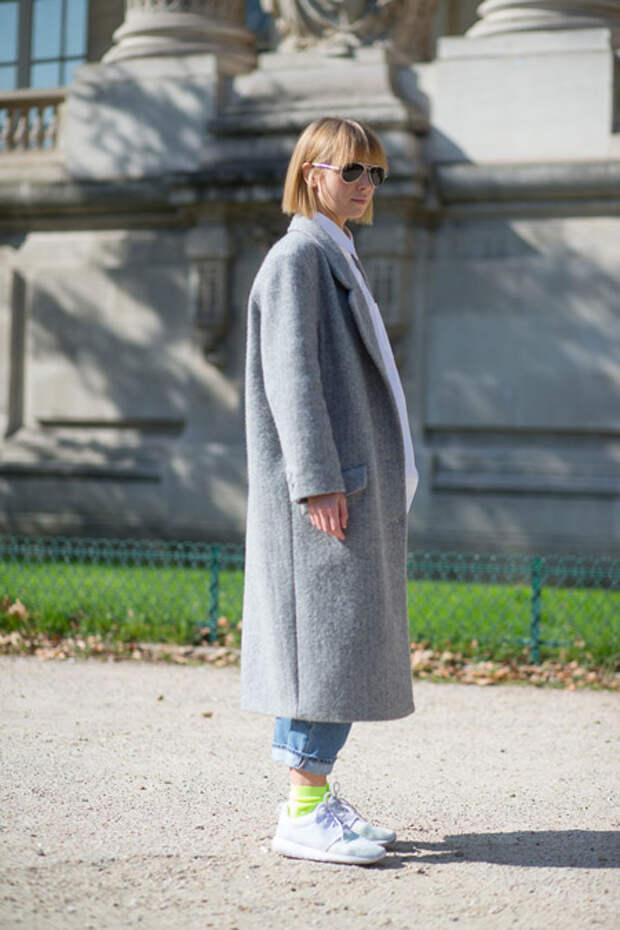 Девушка в длинном пальто и кроссовках