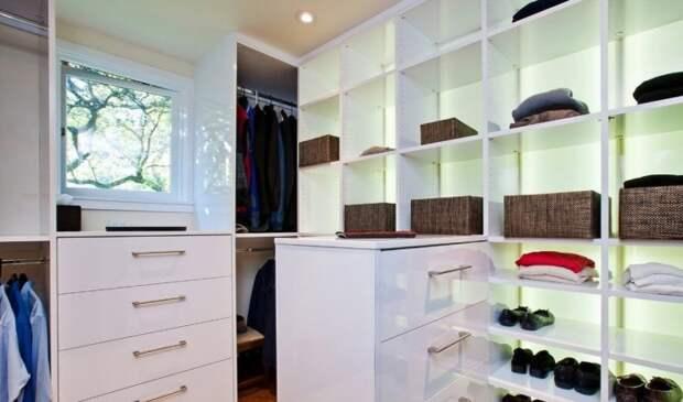 Шкаф светлого оттенка в центре женской гардеробной комнаты.
