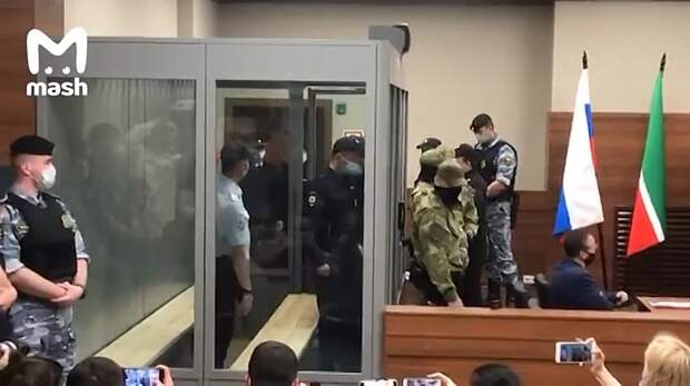 Ильназа Галявиева завели в зал суда. Два сотрудника пристегнуты к нему наручниками....