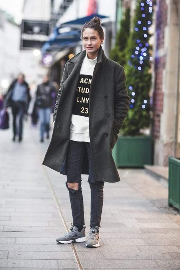 Девушка в рваных джинсах и темном пальто