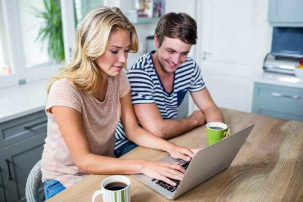 Парень с девушкой сидят за столом перед компьютером с чашками кофе