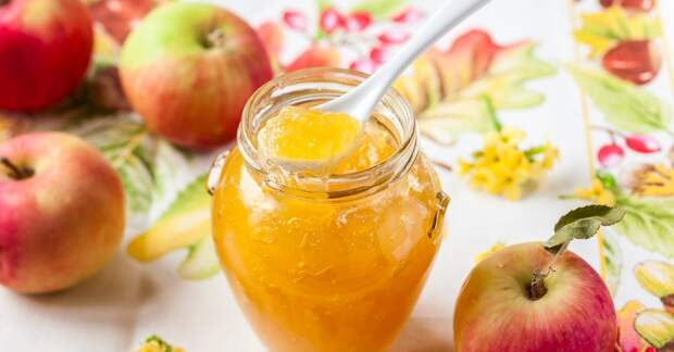 Apple jam in a jar and fresh red apples