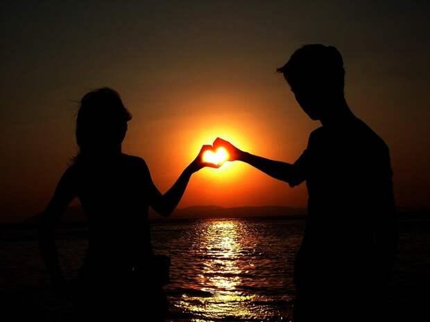 Сердце из рук на фоне солнце