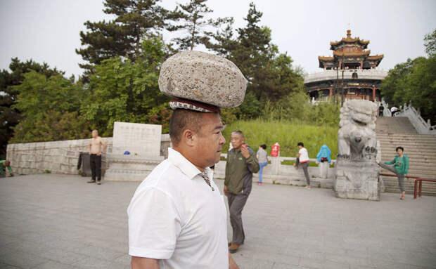 Ради похудения китаец гулял с 40-килограммовым камнем на голове камень, похудение