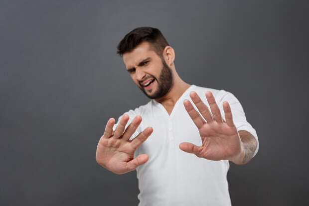 мужчина отгораживается руками