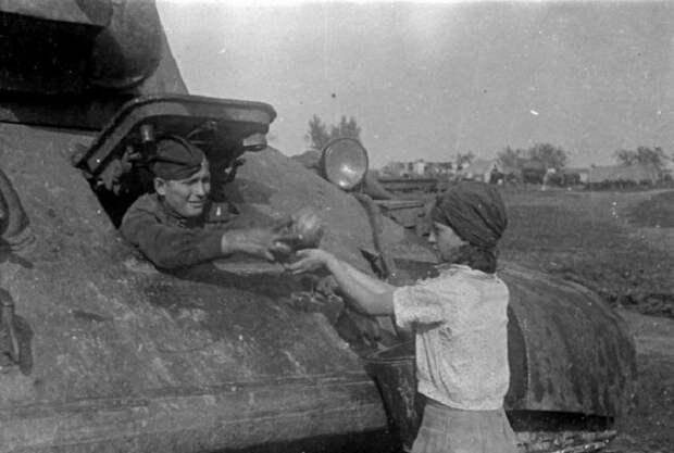 Жительница освобожденного украинского села угощает арбузами механика-водителя танка Т-34, 1943 год.