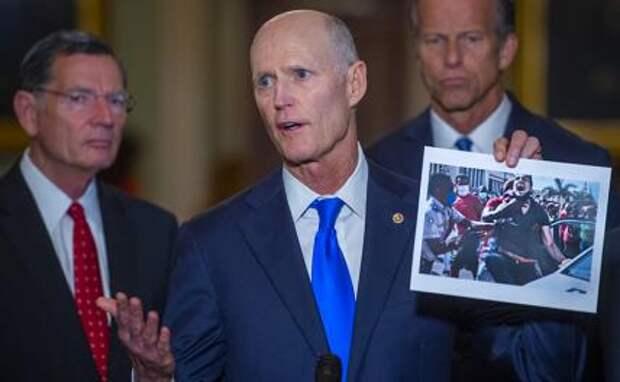 На фото: сенатор США Рик Скотт (республиканец из Флориды) держит фотографию недавней акции протеста на Кубе, делая замечания во время пресс-конференции, Вашингтон, округ Колумбия