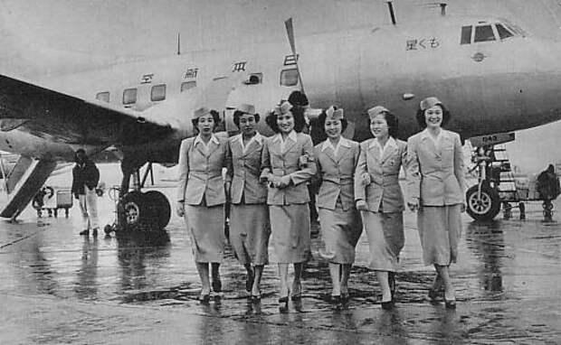 Черно-белая фотография самолета Martin 2-0-2 с шестью бортпроводниками, стоящими перед самолетом